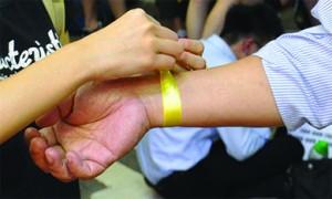 子女為家長帶起黃絲帶,一起參與雨傘運動。