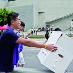 梁柏堅幫忙派發麵包給在金鐘現場的集會人士。