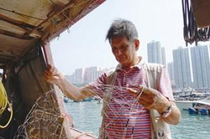 漁民羅金樹展示現代常用的漁網,與當年一樣套上鉛垂。(鍾卓恆攝)