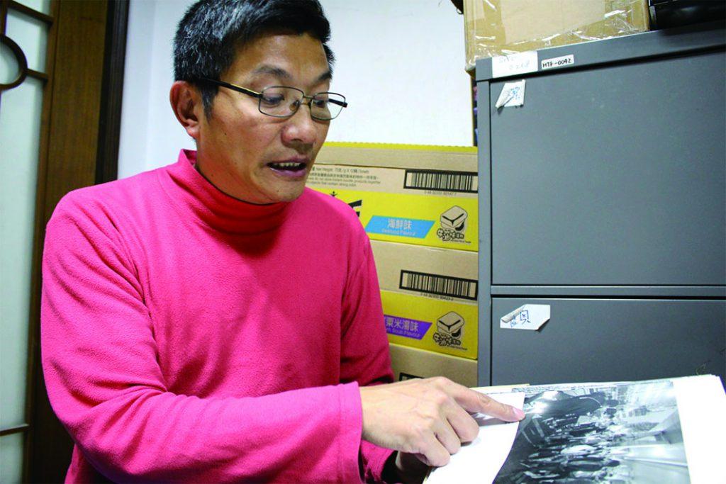 吳衛東向記者展示於天橋底為露宿者舉行悼念會的相片。(盧鳳媚攝)
