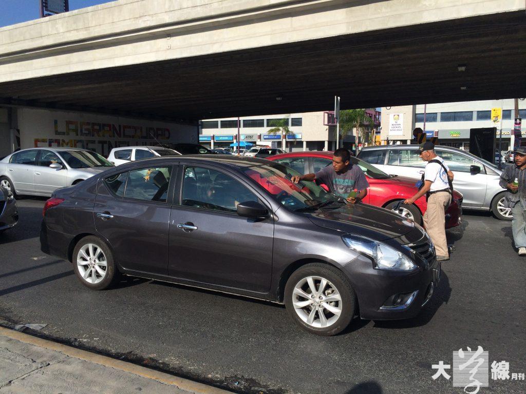 不少墨西哥人拿著清潔劑及抹布,為等待交通燈的車輛抹窗,以賺取幾個錢幣。(陳嘉詠攝)